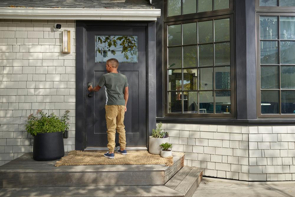 boy entering code on door lock