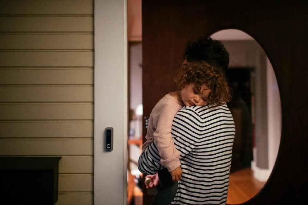 dad holding kid walking in the front door