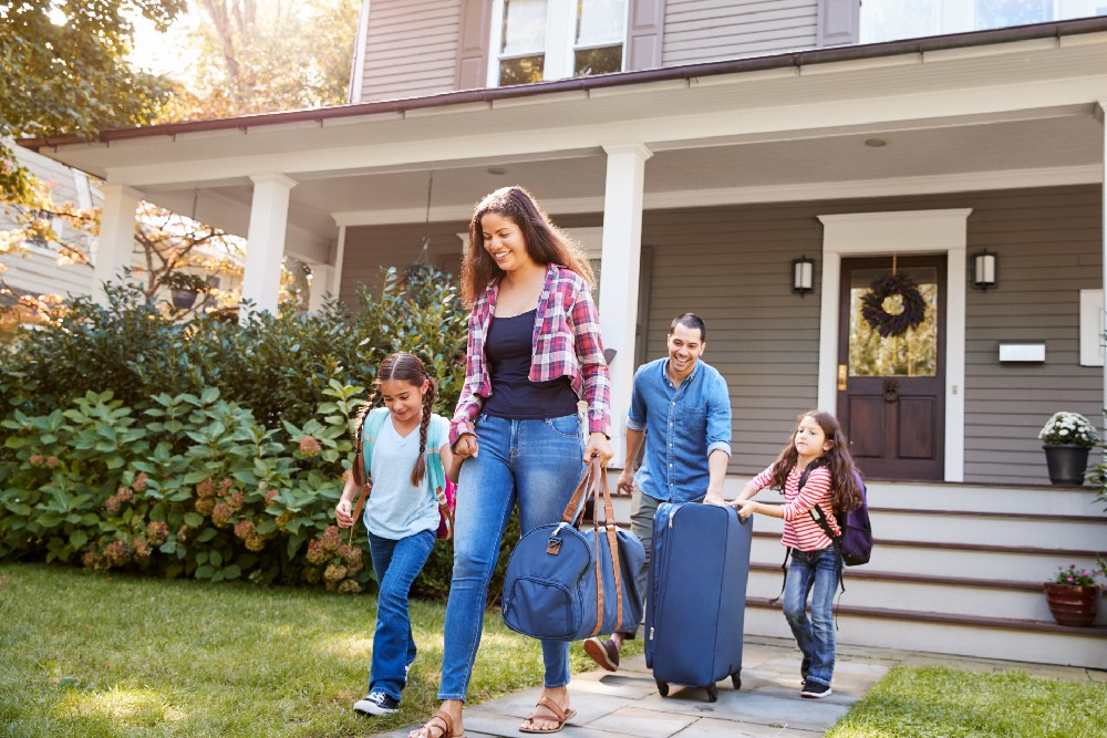 family with luggage leaving home
