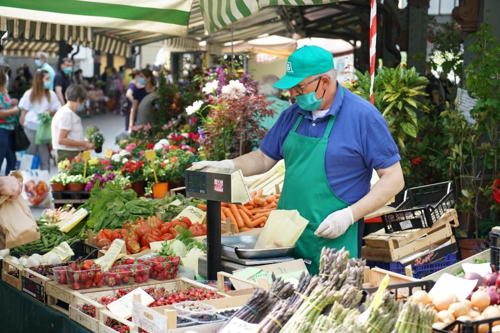 man at farmer's market weighing fruit