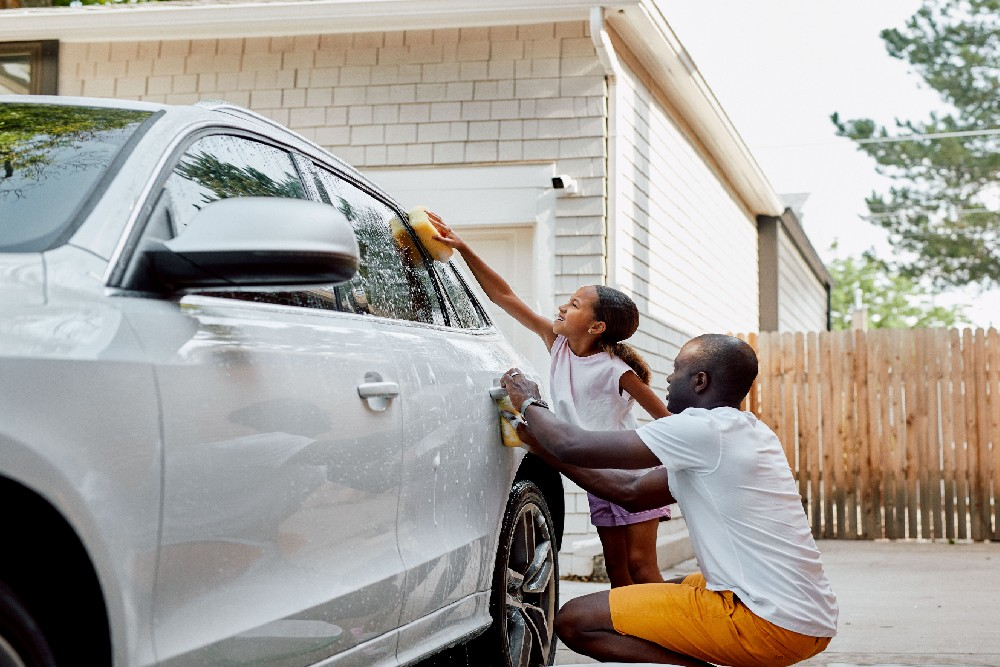 father and daughter washing car with outdoor camera in the background