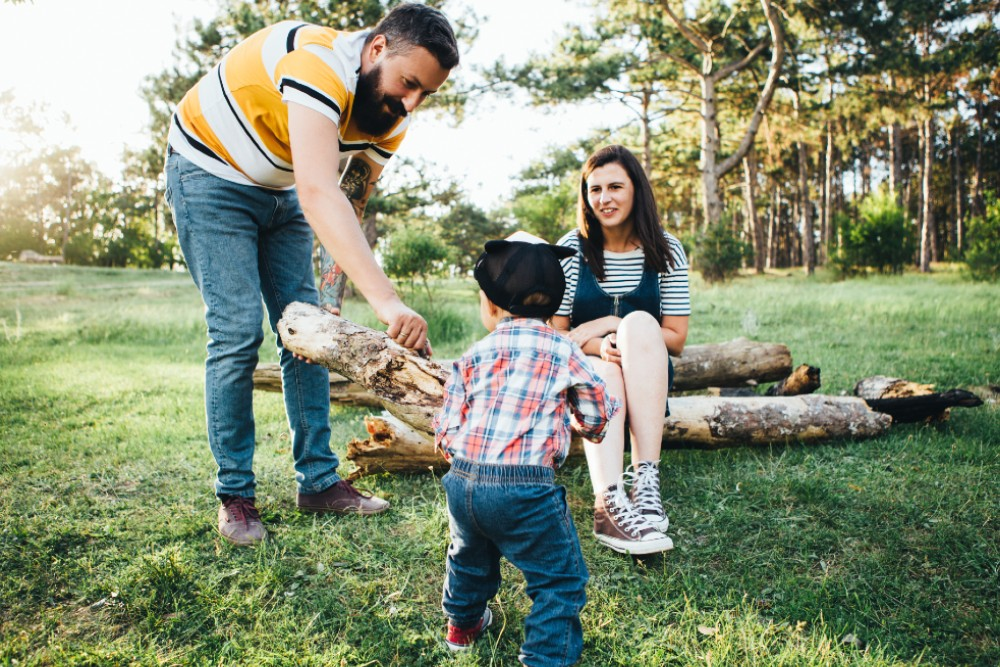 father, mother, and son in the outdoors holding a log