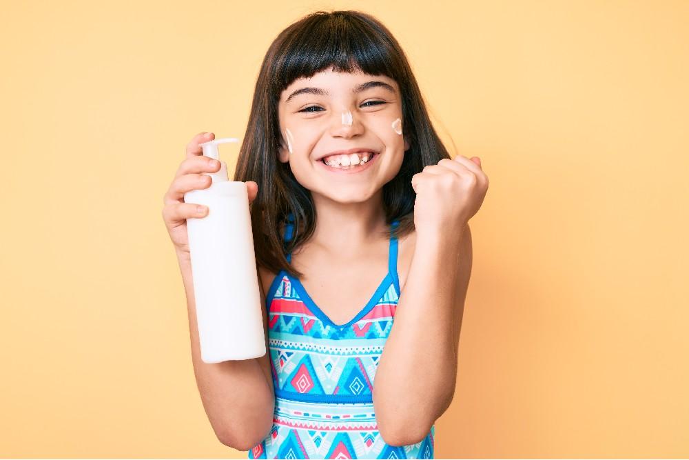 girl holding sunscreen