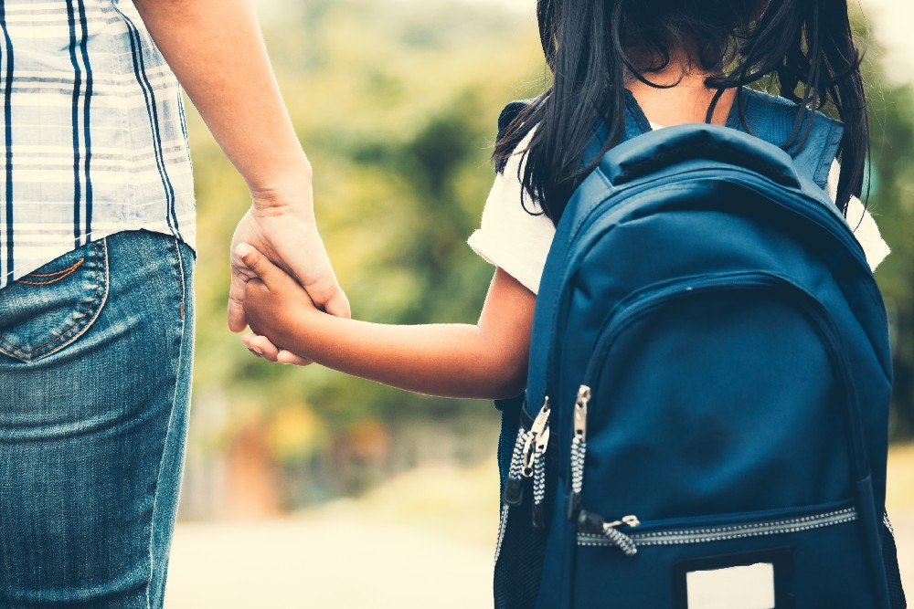 girl in backpack holding hands with mom