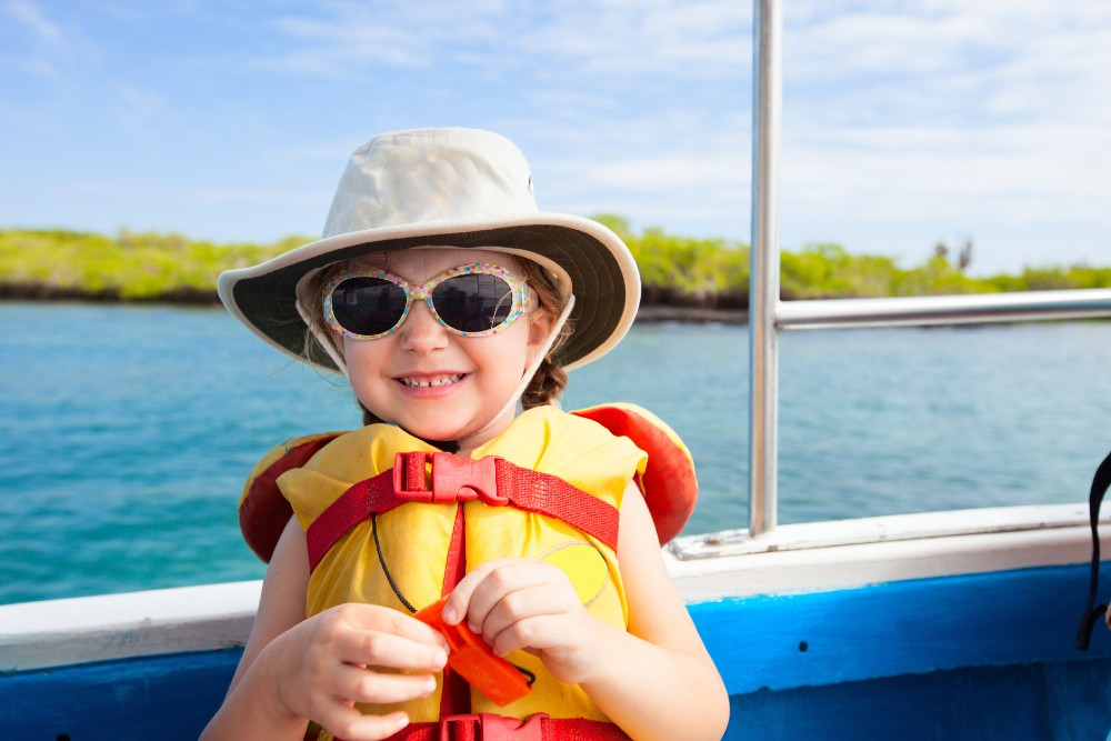 girl in life jacket on boat