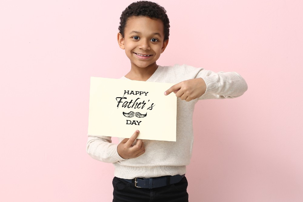 kid holding Happy Father's Day card