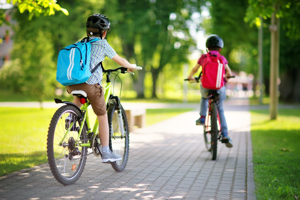 kids riding bikes with backpacks on
