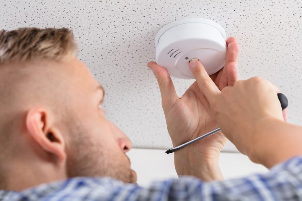 man pressing carbon monoxide alarm