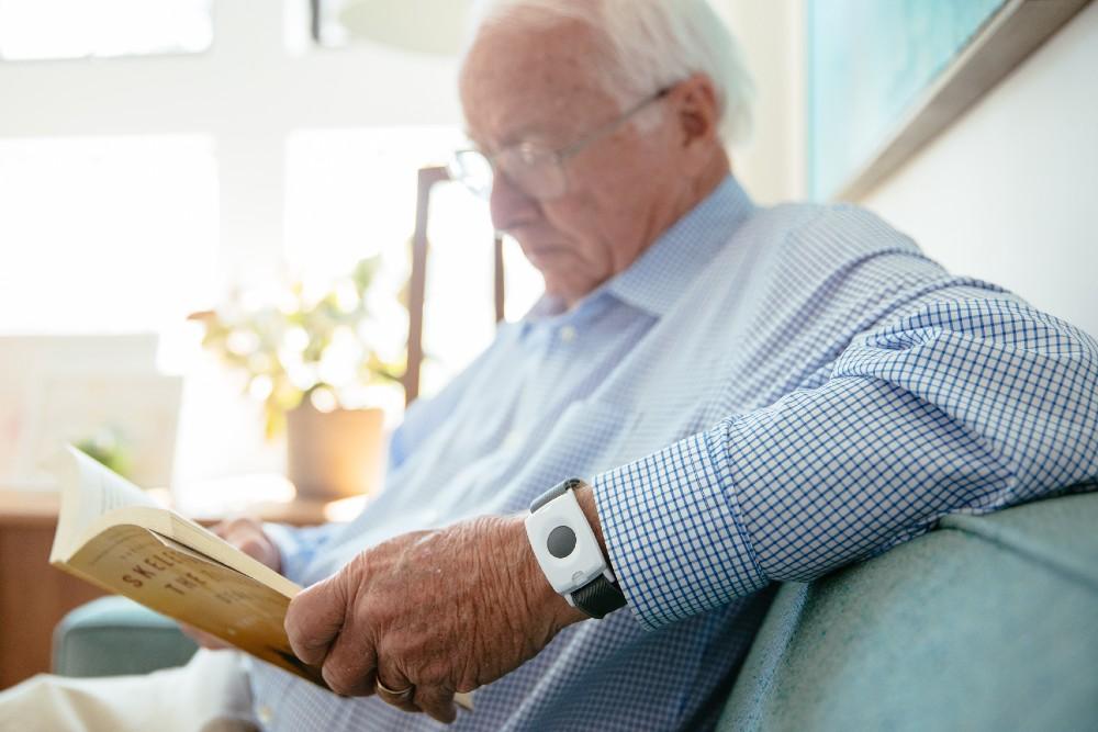 man reading with emergency pendant on wrist