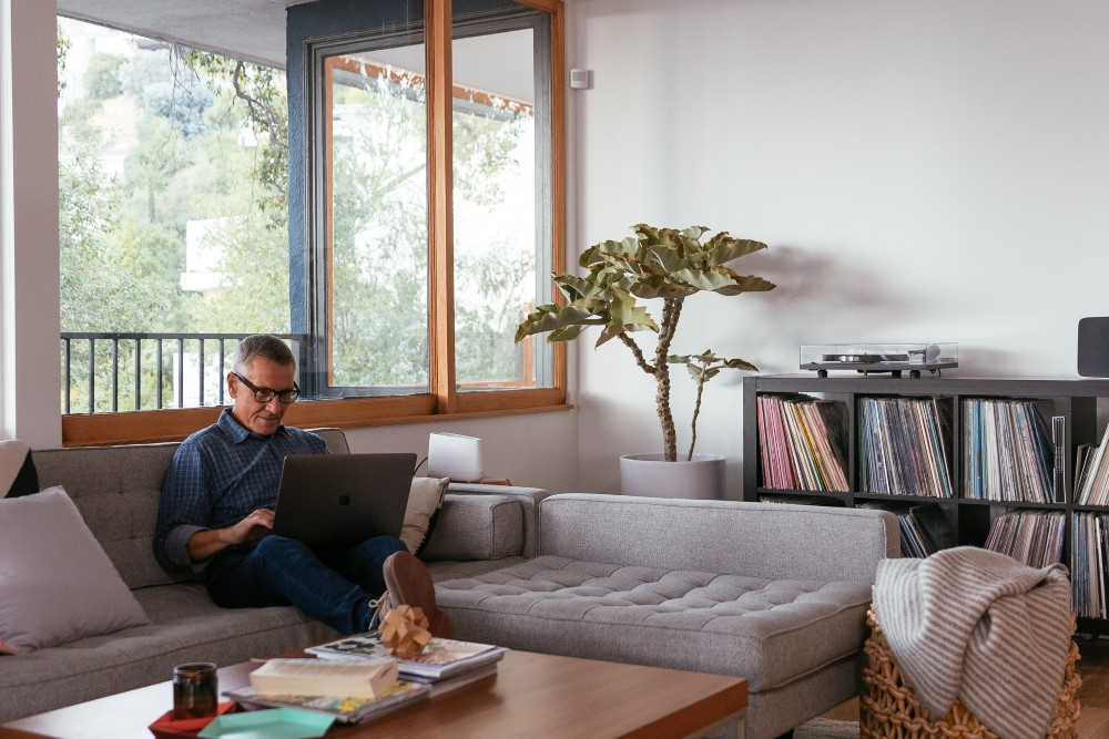 man on couch in living room with laptop