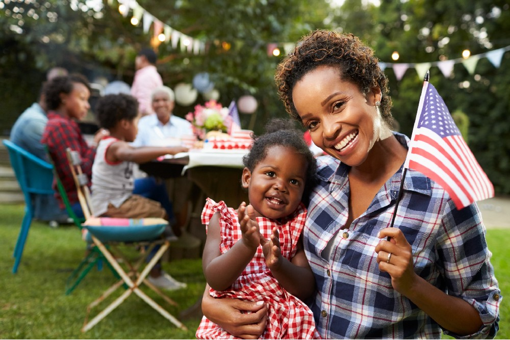 mother and daughter holding flag with family in the background