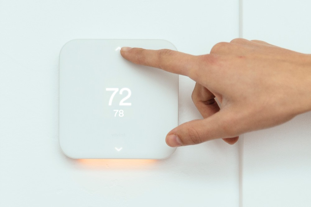 person turning up temperature on Vivint Smart Thermostat