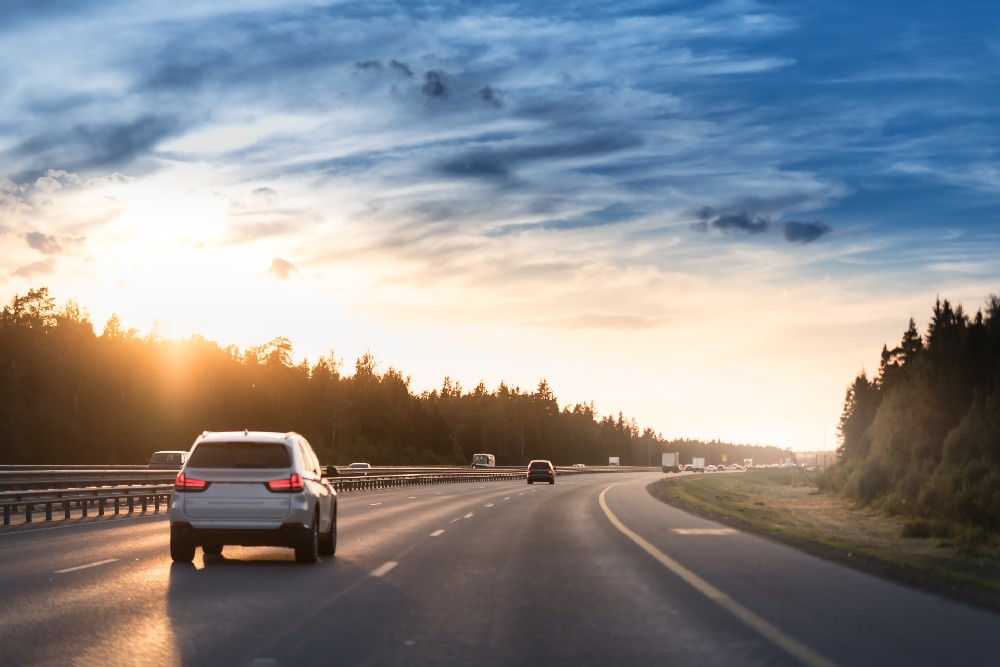 car on freeway with sunset