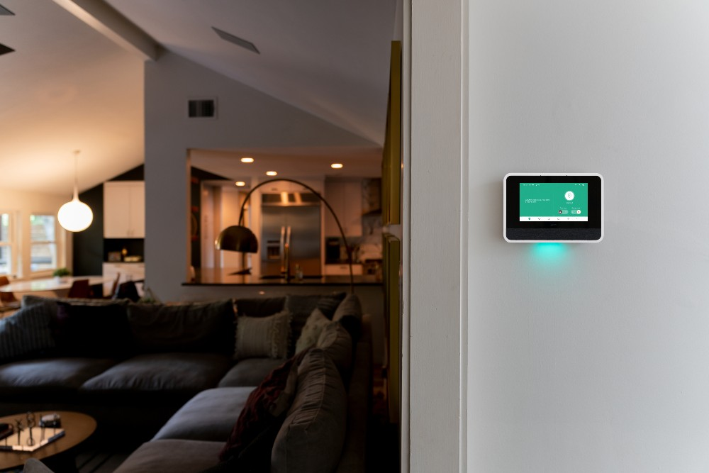 Vivint Smart Hub on a wall while a light illuminates a room in the background
