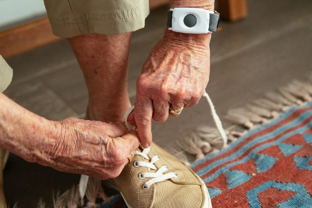 woman tying shoe wearing emergency pendant