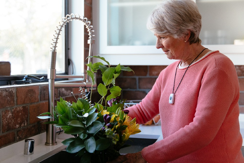 woman at sink wearing emergency pendant