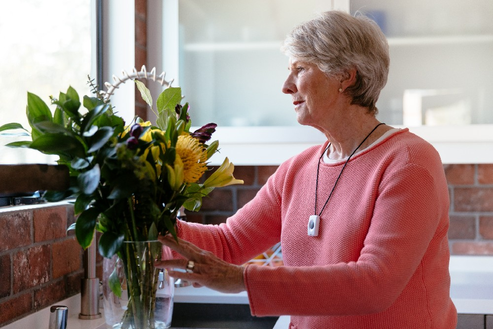 woman with emergency pendant at sink with flowers
