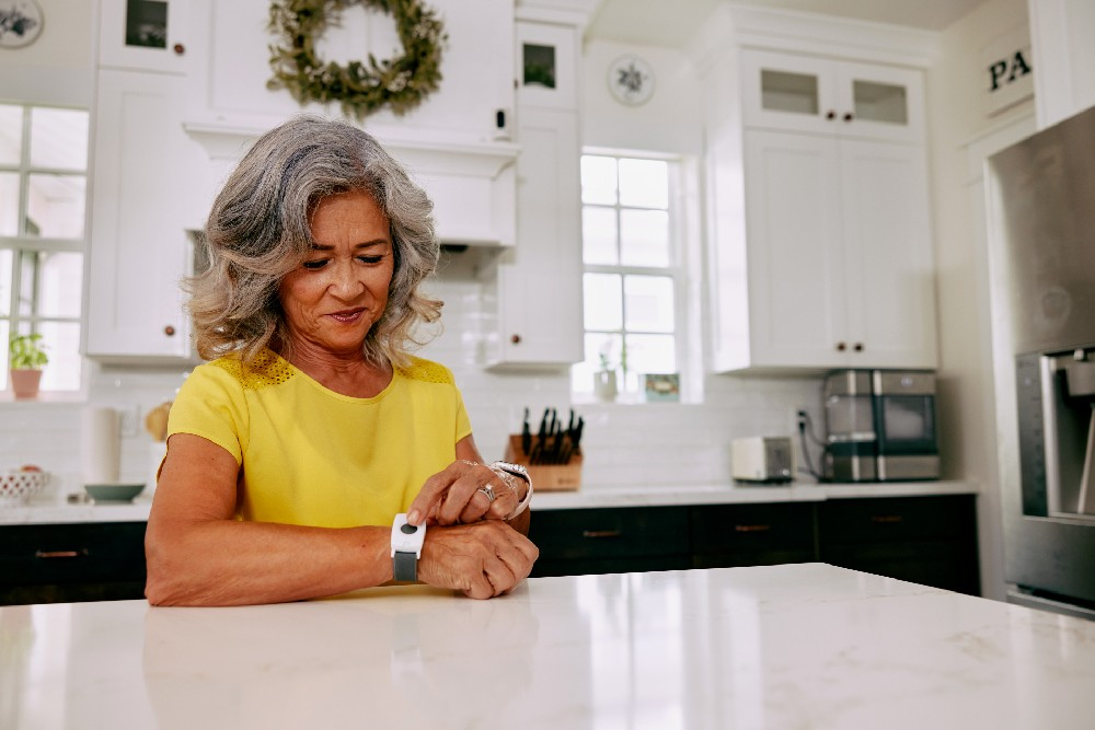 woman with emergency pendant wrist in kitchen