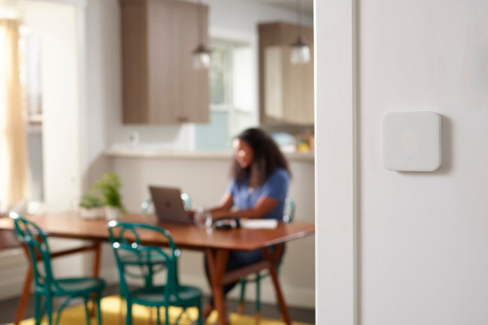 vivint thermostat and woman at table